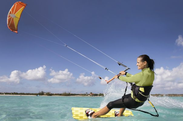 An athletic woman kite boarding in the Caribbean.